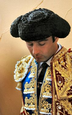 "A montera is the hat traditionally worn by many males & females in the folk costumes of the Iberian peninsula. It has come to name also but not exclusively the ones used by bullfighters, introduced to the ritual event in 1835 by Francisco 'Paquiro' Montes as accompaniment to the traje de luces, or ""suit of lights"". The montera is habitually covered in astrakhan fur with an inner lining of velvet. The image of a saint is sometimes printed on the lining as a talisman of good luck."