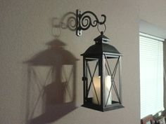 Cheap wall decor idea.   Indoor/outdoor lantern with bracket used for hanging plants