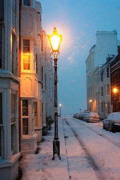 Snow illuminated by a singular lit lamp post.