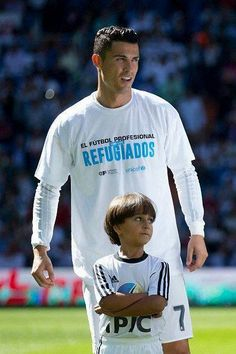 Ronaldo and the rest     Ronaldo and the rest of the Real Madrid squad were all wearing T-shirts expressing their support for the thousands of refugees that have fled their war-torn countries and headed to Europe. | Cristiano Ronaldo Brings Syrian Refugee Boy Onto Soccer Field - BuzzFeed News