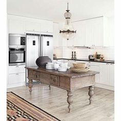 Beautiful antique table crowned with traditional crystal basket chandelier, adding some old world charm to this modern kitchen