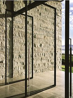 Contemporary glass and steel doors juxtaposed by rustic brick walls.