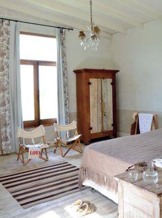 El dormitorio principal, de techos altos y generosas dimensiones, tiene un aspecto austero y cálido a la vez. Sobre la cama, manta de llama, y en el piso, textil del norte argentino a rayas, ambos en to…