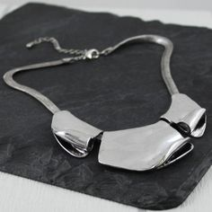 A stunning statement necklace by My Posh Shop.With Jewellery as unique as this, its easy to justify another piece for the collection. This lovely silver metal necklace has a totally unique design. Three polished metal plates with a twisted curl. A short bib style necklace. Versatile enough for a party, a wedding or a business meeting. A gift box is included with this necklace and makes a lovely gift. Take a look at our full collection of fabulous costume jewellery including our popular Metal…