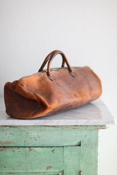 Love this vintage leather duffel on antique distressed farm table with added Carrera Marble top... tasteful