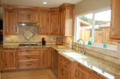 Custom designed kitchen with wood cabinets, tile backsplash, and granite countertops