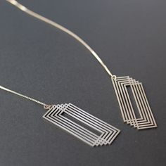 """An Adorn Milk staff fave! MATERIALS Stainless steel pendant, sterling silver box chain MEASUREMENTS Body (includes 2 pendant pieces at each end): 1"""" wide x 2"""" high MORE INFO Before making a purchase,"""