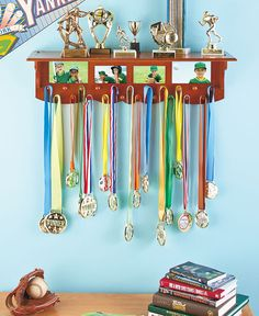 """Could I make this for girls dance pics?  Showcase the shining moments of your sports life on this wooden shelf. Great for athletes in any sport, the Award Shelf (28""""W x 7-7/8""""D x 7-3/8""""H) shows off trophies on the top, hangs medals from the 21 knobs at the bottom and displays pictures in betwee Trophy Shelf, Trophy Display, Award Display, Display Shelves, Shelving, Display Ideas, Hanging Medals, Trophies And Medals, Hockey Trophies"""