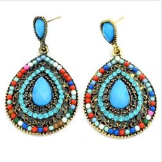 Beaded Filigree Drop Earrings in a beautiful combination of aqua teardrop center stones accented with matching crystals and tiny multi-colored accent beads. Intricately crafted for a hand made, artisa