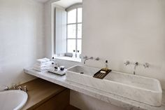 The architects fitted the master bath with a double trough sink fabricated locally by a marbrier (who also built the kitchen island). The bathtub is set into an oak bench that extends under the sink.