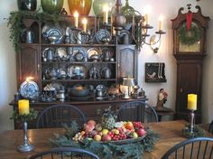 A Pewter Cupboard, a Tall Case Clock with a Simple Green Wreath hung from Red Ribbon, and a Large Trencher with Stone Fruit.
