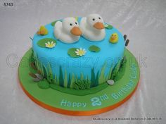Duck Pond Cake. Quack Quack... Round childrens ducks on the pond cake with mummy and daddy ducks, and three little ducklings. Finished with water lilies, reeds, bulrushes and foliage.