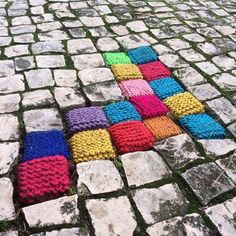 Yarn bombing. Knitted squares on cobbled street.