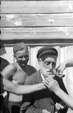 German soldiers cutting an old jew beard. The victim suffers silently, humiliated. Ukraine 1941