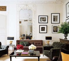 Overstuffed furniture and black and white photos add drama to this Paris living room.