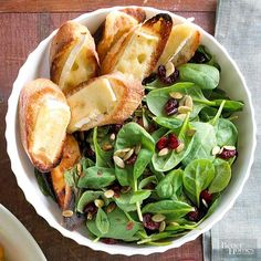 Slices of Brie cheese-topped toast accompany a spinach-based Thanksgiving salad topped with creamy cranberry dressing.