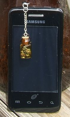 "Fill this teeny bottle with anything you want to keep close to you. It comes filled with dried flowers. At only $6 this is a deal to have the tiniest bottle (1 3/8"" from top of cork) ever attached to your phone."
