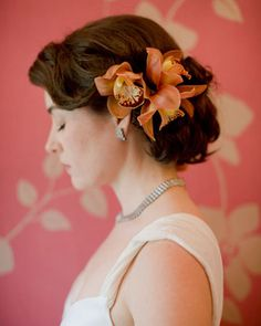 A beachy updo accessorized with orange orchids
