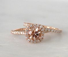 Beautiful and dainty 14K rose gold diamond cushion halo ring SET centering a gorgeous champagne pink round brilliant cut morganite measuring 6.5 mm and weighing approximately 1.20 cts., VS clarity stone, great cut, color and shine.  The engagement ring on this set has diamonds with a total carat weight of approximately 0.40 ct. The band is set with round brilliant cut diamonds weighing 0.30 ct. Approximate total carat weight of the diamonds: 0.70 cts. All diamonds are natural and untreated…