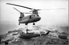 """At a hilltop firebase west of Chu Lai in Vietnam, a huge army """"Chinook"""" helicopter prepares to lift a conked-out smaller one to a base for repairs, April 27, 1969."""