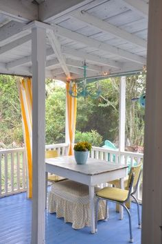 Odd chairs and an ottoman w/little square table on a screened porch at Jane Coslick Cottages