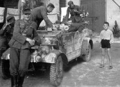 A Italian boy photo bombing some German soldiers taking a photo with their VW Type 82 Kubelwagen