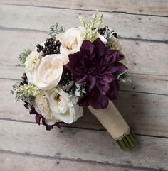 This rustic wedding bouquet is arranged with blush and ivory garden roses and dahlias, with larger pops of plum dahlias, accented with soft green dusty miller and deep purple berries. This wedding bou