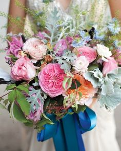 This vibrant bouquet, which grouped together garden roses, nigella, and dusty miller, was tied with a pair of deep blue satin ribbons for a loose, organic feel.