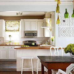 kitchen remodel ideas: beaded board under counters, white cabinets, large pendulum light fixture, wood countertops