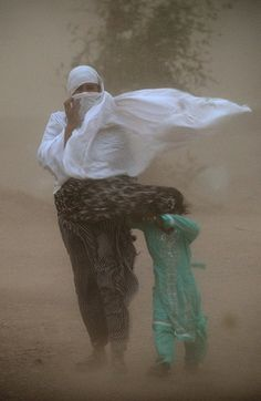 Islamabad, Pakistan - A woman and child struggle to walk in a dust storm.