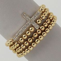 """Gold Beaded Crystal #CrossBracelet. This 1"""" H bracelet compliments any wrist when worn! Four rows of shining gold beads surround a 2"""" L by 1"""" W sideways gold crystal encrusted cross that sparkles remarkably. This #bracelet also features an elastic band that stretches for a comfortable fit. DETAILS: http://www.lolafashionaccessories.com/products/Gold-Beaded-Crystal-Cross-Bracelet.html $16.99"""