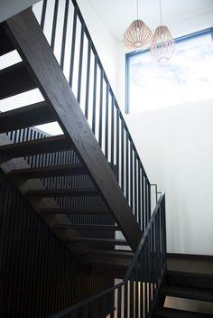 Eine zeitgenössische dunkle Holztreppe führt Sie nach oben und ein großes Fenster flutet den Raum mit natürlichem Licht.