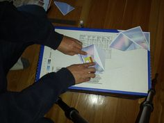 Slide 7 - Keep the smaller flap open and fold the just glued flap to the center.  Apply a sliding pressure from the bottom of the envelope to the top of the flap until it is affixed to the inner flaps.  This will only take a few seconds.