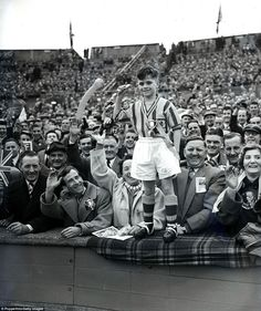 An immaculately turned out young Aston Villa fan has pride of place in the crowd for his team's FA Cup final appearance in 1957, when the opponents were Manchester United.