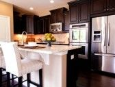 Modern kitchen with dark wood cabinets and hardwood floors. stock photography
