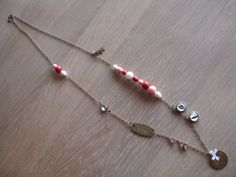 Grandmother's long necklace with a special meaning. The cabochons with a and t are for my youngest grandsons, next is hammered plate with the name of my oldest grand daughter. As  she is the only girl I have put a creamy bow on top. Then there is a hammered plate with the name of my oldest gtandson. A long the chain are symbols which means how precious this children are for me. For sale via www.misspiggyspearls.com