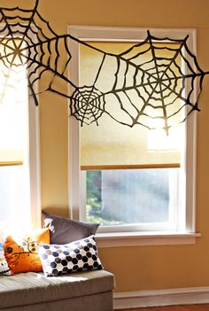 Halloween decor: Use a cut-paper snowlfake technique to make spiderwebs out of garbage bags. #DIY #halloween