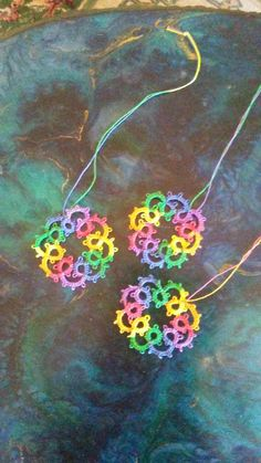 Set of three rainbow colored medallions. Long threads attached for hanging as ornaments. Hand tatted.