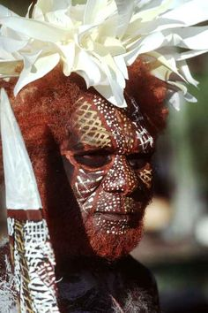 A Bathurst Island man painted up for a traditional Tiwi dance during the Festival of Pacific Arts in Tahiti; he has elaborate face painting, red ochre in his hair and beard, a headdress of white cockatoo feathers and carries a magnificently carved spear.