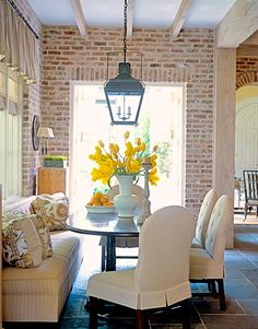 Breakfast nook - exposed brick, covered chairs, lantern pendant, yellow pop