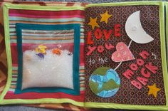 hand made quiet book.  i spy page.  moon snaps, heart slides back and forth and earth twists