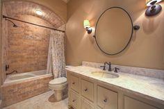 Bathroom with brick shower and bathtub.
