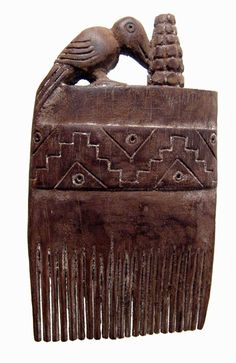 Ancient wooden comb from Chancay, Peru, dating back to AD 1000- 1500 with a parrot pecking a stalk of corn