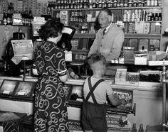 Huisvrouw en haar zoontje in de winkel voor de toonbank bij de kruidenier, Haarlem, 18 april 1952.