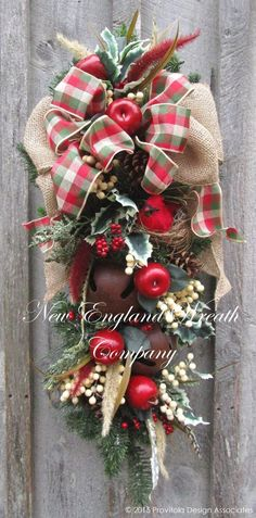 Lexington Holiday Swag. Silk pine boughs create a lush background for abundant berry clusters, holly leaves, fox tails, small apples and pine cones. A plush double layer bow in burlap and plaid ribbon