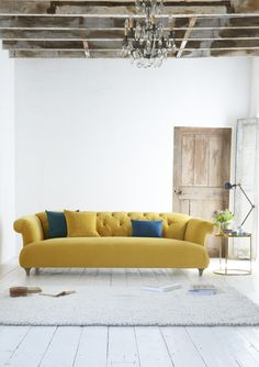 Loaf's deep-buttoned Dixie chesterfield sofa in a bright and sunny Bumblebee yellow velvet in this beautiful living room with white-washed walls and exposed beams