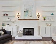 Lovely bedroom features a black fireplace lined with a wood mantle under a black and white horse art flanked by stacked floating shelves and built-in cabinets alongside a seagrass chair. Stucco Fireplace, Fireplace Shelves, Fireplace Built Ins, White Fireplace, Living Room With Fireplace, Fireplace Design, Fireplace Mantels, Mantel Shelf, Diy Mantel