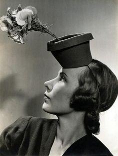 Onbekend | Hoeden mode. Vrouw showt hoedje in de vorm van een bloempot met bloemen. Plaats en jaartal (1940?) onbekend.