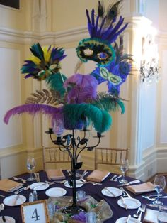 Tall feather centerpiece idea for masquerade party using color of preference...
