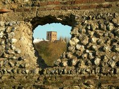 Norman tower of St Albans Cathedral seen through a hole in the Roman wall
